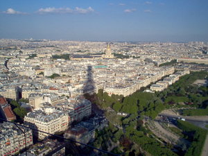 A Parisian view from the second level of the Eiffel Tower, with  creeping at the horizon, barely past the towering shadow.